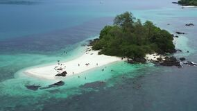 Aerial view drone shot of peoples on a tropical small island with trees, rocky and white sand beaches in the middle of the ocean.