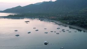 Aerial view from drone, stony seacoast and mountains on a sunset. Indonesia. Bali. stock video