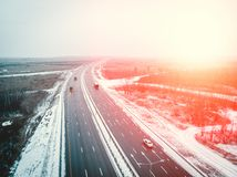Aerial view from drone to winter asphalt highway or motorway road in countryside with car and truck traffic driving fast. Red sunlight toned with copy space stock image