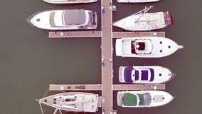 Aerial View by Drone of Yacht Club and Marina. Top view of yacht club. White boats in sea water. Marina dock yachts and. Small moto. Yacht and sailboat stock footage