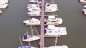 Aerial View by Drone of Yacht Club and Marina. Top view of yacht club. White boats in sea water. Marina dock yachts and stock footage