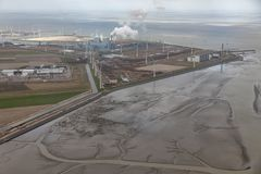 Aerial view Dutch Eemshaven with coal powered electricity plant. Aerial view Dutch Eemshaven near Wadden sea with wind turbines and coal powered electricity stock image