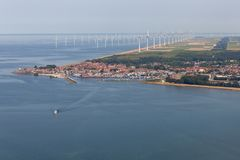 Aerial view Dutch fishing village with offshore windfarm along coast royalty free stock image