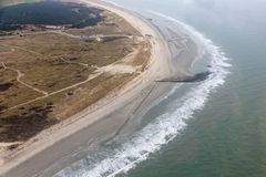 Aerial view Dutch island Ameland with beach and lighthouse. Aerial view seaside Dutch island Ameland with beach, lighthouse and holiday homes in the dunes royalty free stock image