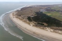 Aerial view Dutch island Ameland with beach and lighthouse. Aerial view seaside Dutch island Ameland with beach, lighthouse and holiday homes in the dunes stock photography