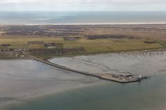 Aerial view Dutch island Schiermonnikoog with pier and ferry terminal. Aerial view Dutch island Schiermonnikoog with pier ferry terminal at low tide stock photos