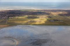 Aerial view Dutch island Schiermonnikoog with shining sunlight. Aerial view Dutch island Schiermonnikoog while the sunlight is shining at the fields stock photography
