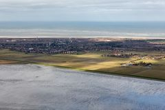 Aerial view Dutch island Schiermonnikoog with shining sunlight. Aerial view Dutch island Schiermonnikoog while the sunlight is shining at the fields stock images