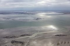 Aerial view at Dutch Wadden Sea with low tide. The sun is reflecting at the water royalty free stock photography