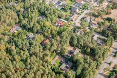 Aerial view of the edge of a village with small family houses, whose properties penetrate into the dense forest. royalty free stock photos