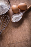 Aerial view eggs flour in spoon bowl corolla Royalty Free Stock Photo