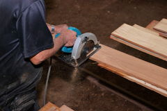 Aerial view of electric circular saw is being cut a piece of wood against hands of senior carpenter in carpentry workshop. Royalty Free Stock Photo