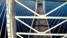 Aerial view elements metal structure cable stayed car bridge in modern city. Urban car traffic at suspension bridge on background city infrastructure stock footage