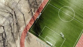 Aerial view of empty green football field with trees and their shadow. Running track Stock Image