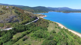 Aerial view of empty paved road passing artificial lake of Peruca, Croatia. Aerial view of empty paved road through mountains passing artificial lake of Peruca stock video footage