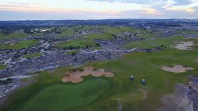 Golf course from drone. Aerial view of evening golf course. The people are playing golf at the field. Beautiful end of sunset and orange cloudy sky at the stock video footage