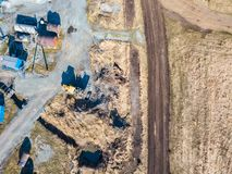 Aerial view of an excavator and yellow tractor transporting crushed stone, cement and sand during the extraction of minerals from royalty free stock photo