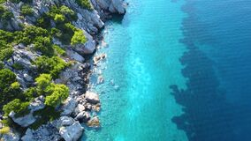 Aerial view of exotic sea coast with rocks and greenery and amazing transparent sea with various shades of blue color