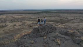 Aerial view. The family standing on the mountain. Mother, father and son went hiking in the mountains. Sunset. stock video footage