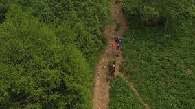 Men and women enjoy adventure. Kid sits in hiking carrying. Aerial view. Family trekking on picturesque green slope. Tourist walk with backpacks and trekking stock video footage