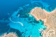 Aerial view famous Blue Lagoon in the Mediterranean Sea. Comino Island, Malta. Beach and vacationers, a bay pier with ships and stock photography