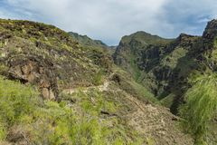 Aerial view of famous Hell gorge in Adeje. Sunny day. Blue sky and clouds above the mountains. Rocky tracking road in dry mountain. Area. Tenerife, Canary royalty free stock image
