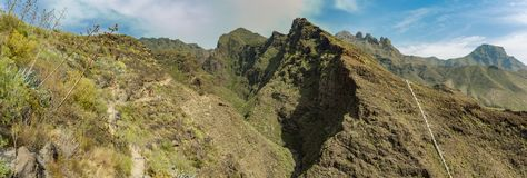 Aerial view of famous Hell gorge in Adeje. Sunny day. Blue sky and clouds above the mountains. Rocky tracking road in dry mountain. Area. Tenerife, Canary royalty free stock photo