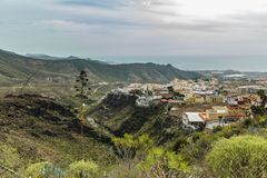Aerial view of famous Hell gorge and Adeje town in the south of Tenerife. Sunny day. Blue sky and clouds above the mountains. Rocky tracking road in dry royalty free stock photography
