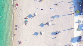Aerial view of famous white party beach of Pag island, Croatia. Aerial view of people sunbathing and swimming on famous white party beach of Pag island, Croatia stock video footage