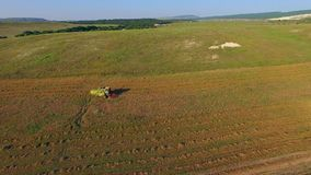 AERIAL VIEW. Farm Machinery Cutting Field At Harvest stock video footage