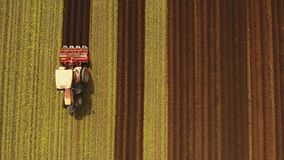 Tractor cultivates the land in the field. Aerial view Farmer in tractor preparing land with seedbed cultivator in farmlands. Tractor plows a field. Agricultural stock footage