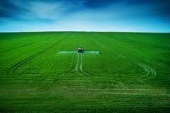 Aerial view of farming tractor plowing and spraying on field stock photography