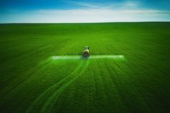 Aerial view of farming tractor plowing and spraying on field stock photos