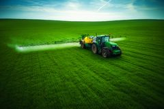 Aerial view of farming tractor plowing and spraying on field royalty free stock photography