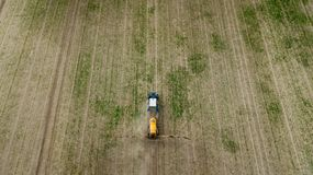 Aerial view of farming tractor plowing and spraying on field royalty free stock photos