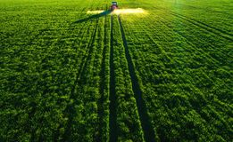 Aerial view of farming tractor plowing and spraying on field royalty free stock images