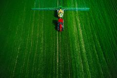 Aerial view of farming tractor plowing and spraying on field stock images