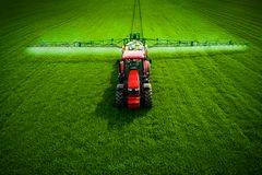 Aerial view of farming tractor plowing and spraying on field stock image