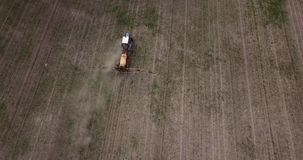 Aerial view of farming tractor plowing and spraying on field stock video footage