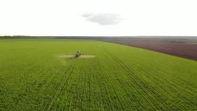 Aerial view of farming tractor spraying on field with sprayer, herbicides and pesticides at sunset. Farm machinery stock footage