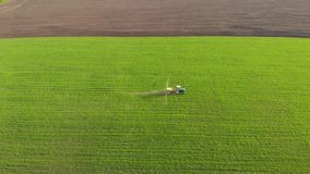 Aerial view of farming tractor spraying on field with sprayer, herbicides and pesticides at sunset. Farm machinery stock video footage