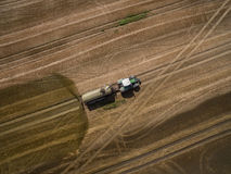 Aerial view of a farming tractor with a trailer fertilizes a freshly plowed agriculural field with manure Royalty Free Stock Photos