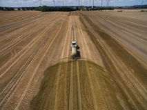Aerial view of a farming tractor with a trailer fertilizes a freshly plowed agriculural field with manure Royalty Free Stock Images