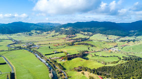 Aerial view on a farmland at the foot of mountain ridge. Coromandel, New Zealand. New Zealand has one of the best environment for agriculture in the world Royalty Free Stock Photos