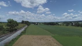 Aerial view of farmlands and countryside  with a railroad track on a beautiful sunny summer day stock video footage
