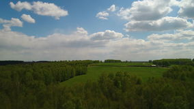 Aerial view of field and forest, clouds, farm stock video footage