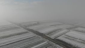 Winter came. Aerial view of fields are covered with snow and old cemetery near the road. stock video footage