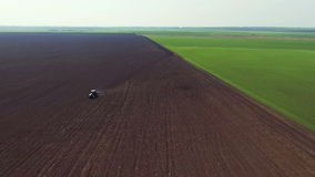 Aerial view of fields, tractor plowing the soil in spring day, distancing stock video footage