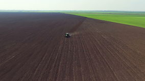 Aerial view of fields, tractor plowing the soil in spring day, distancing, zoom stock video footage