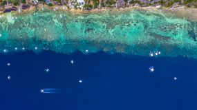 Aerial view of Filipino boats floating on top of clear blue waters, Moalboal is a deep clean blue ocean and has many local. Filipino boats in the sea. Moalboal stock photo